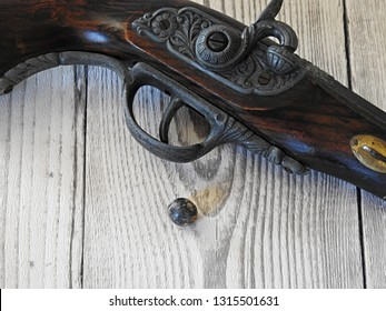 One pistol, one shot: Detailed closeup of mechanics of antique wooden flintlock pistol displayed on white wood surface background and single musket ball (bullet). Decorative vintage weapon concept