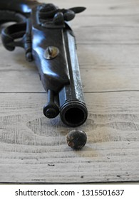 One pistol, one shot: Textured closeup of single musket ball (bullet) displayed on white wood surface/background by the barrel of a blurred wooden antique flintlock pistol. Historic weapon concept