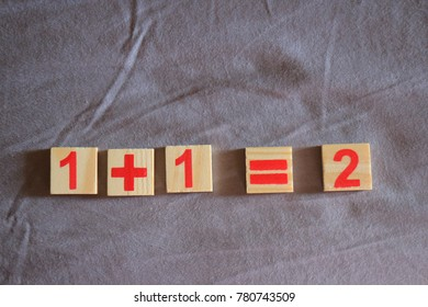 one plus one  equal two by wood block digit