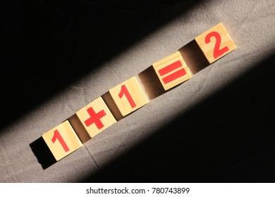 one plus one  equal two by wood block digit in the light