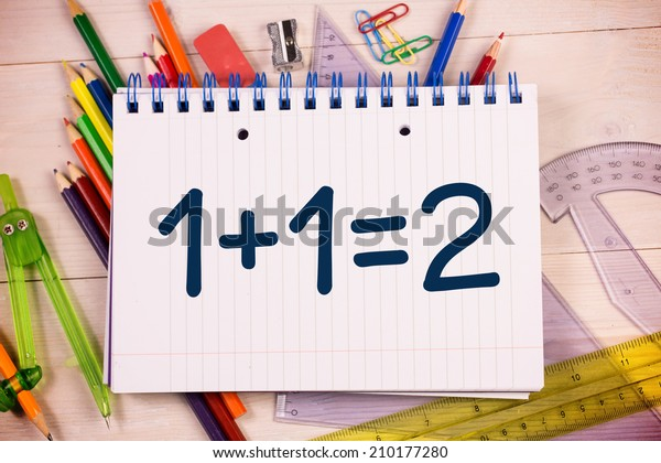 One plus one equals two on notepad against students desk