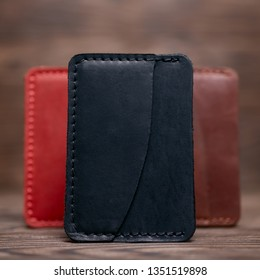One pocket black leather handmade cardholder. On blurred background stay other colour cardholders. Stock photo on blurred background.