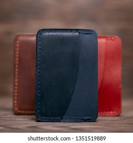 One pocket blue leather handmade cardholder. On blurred background stay other colour cardholders. Stock photo on blurred background.