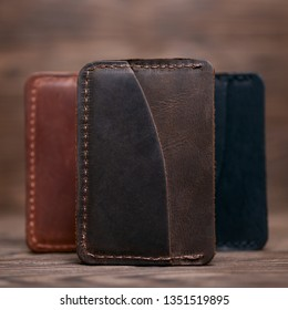 One pocket brown leather handmade cardholder. On blurred background stay other colour cardholders. Stock photo on blurred background.