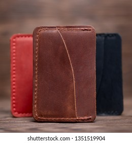 One pocket ginger colour leather handmade cardholder. On blurred background stay other colour cardholders. Stock photo on blurred background.