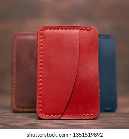 One pocket red leather handmade cardholder. On blurred background stay other colour cardholders. Stock photo on blurred background.