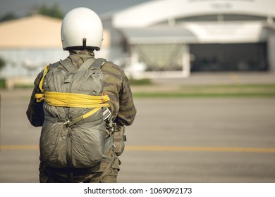 one police aerial reinforcement unit in camouflage uniform and helmet with T-10 static line parachute  and equipment standby at airfield in cinematic tone with copy space