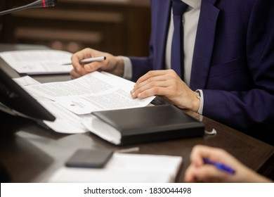 One of politician sitting by table with his hands over document during political summit or conference