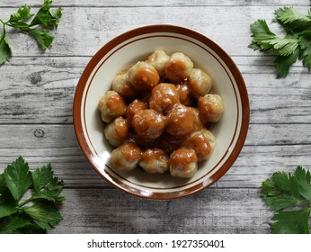 one porse of cilok in the brown plate with white wooden as background flat lay