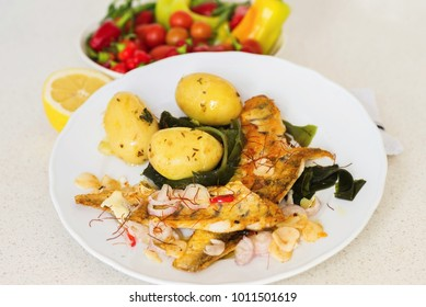 One portion of roasted fish zander, boiled potato and seaweed wakame, one portion on plate, raw vegetable in bowl, sliced lemon, cutlery.