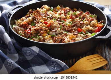 one pot dish - Beef and  long grain rice with Vegetables, corn kernels and spice in cast iron pan, easy and quick recipe, view from above, close-up