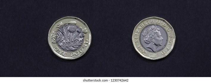 One pound coin minted in 2018. Isolated on black background