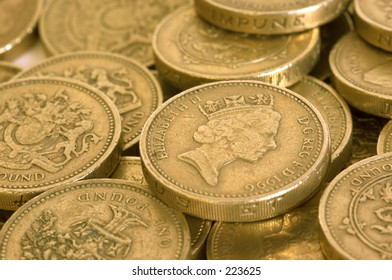 One pound coins scattered on a surface.  Close up.