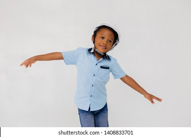 One preschool African American boy wearing engineer hard hat with outstretched hands and spread wings flying in white isolated background