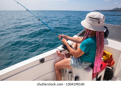 One pretty girl have fishing on sailboat, deep-sea fishing trip, holding rod in hands