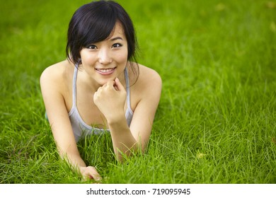 one pretty young asian woman on grassland