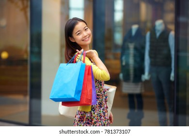 one pretty young asian woman holding shopping bags in the street