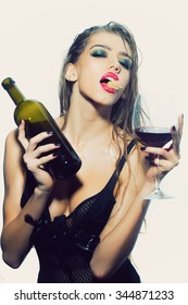 One pretty young sexy woman in black underwear with long wet hair holding wine bottle glass and cork in mouth standing in studio on white background, vertical picture