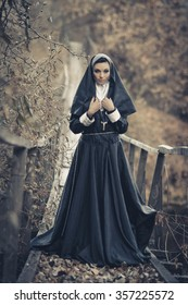 One pretty,sexy nun,cute nun,peaceful nun,alone,posing nun,attractive nun,young nun,holy nun,sister with a cross outdoors,forest,old,wooden suspension bridge with frightening view,special uniform,veil