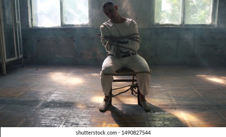 One psycho man sitting being tied to a chair in mental hose