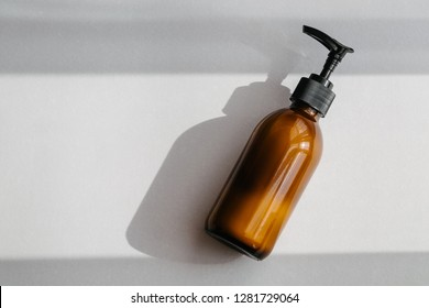 One pump dispenser glass brown bottle for cosmetics, overhead. Direct light. Beauty blogging, salon treatment, minimalism concept