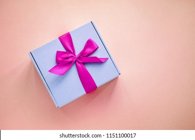 One purple paper box with bright pink ribbon bow on colored background from above. Minimalism, copy space