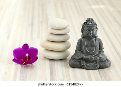 One purple phalaenopsis orchid flower, pebbles cairn, five white stones, small Buddha sculpture