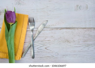 One purple tulips on yellow napkin and cutlery on white wooden background with copy space
