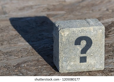 One question mark written on a square stone