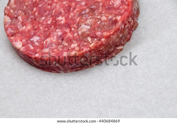 One raw red meat burger for hamburger of minced ground beef or pork on white parchment paper ready for cooking