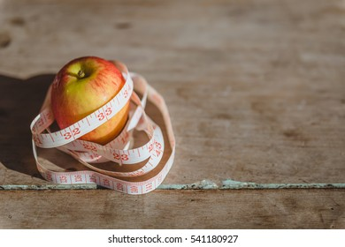 One red apple and tape measure placed on the old wooden.