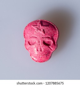 One Red Army Skull, Ecstasy, MDMA or medication pill shaped like a skull on a grey  background.