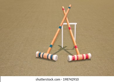 One red, and one blue croquet mallet resting against a hoop