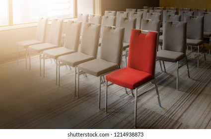 One red chair different from others in empty conference room
