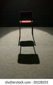 one red chair on stage, lighted with one spot light, empty seats in background