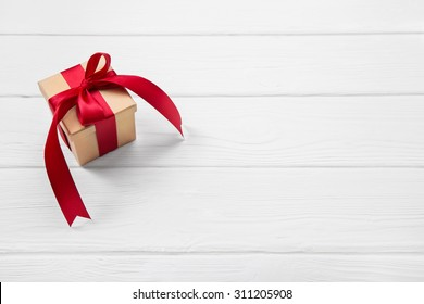 One red christmas present on white wooden background with a big ribbon.