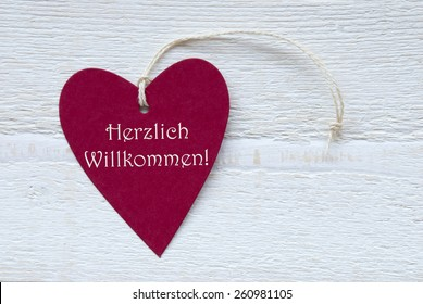 One Red Heart Label Or Tag With White Ribbon On White Wooden Background With German Text Herzlich Willkommen Means Happy Welcome Vintage Retro Or Rustic Style