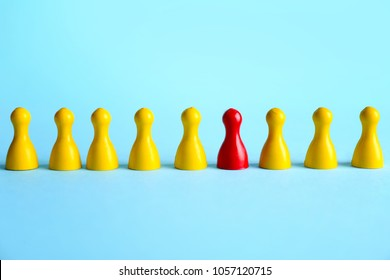 One red pawn among yellow ones on blue background. Difference and uniqueness concept