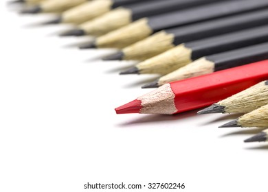 One red pencil among many black pencil