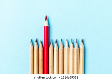 One red pencil standing out from the series of colorful pencils. On blue background. Sign symbol idea concept of leadership, divergent, diversity. Standoff of the individual to society