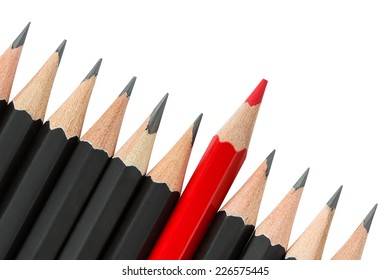 One red pencil standing out from the row of black pencils