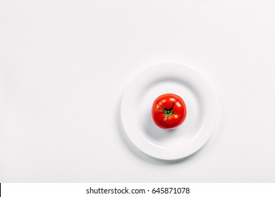 One red tomato on a white plate isolated on white. Top view. Copy space for your text.