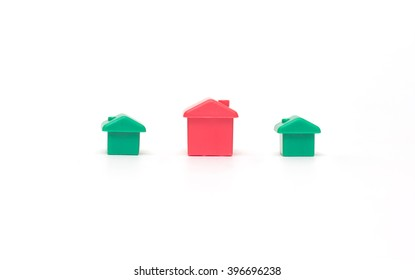 One red toy house and two green on a white background