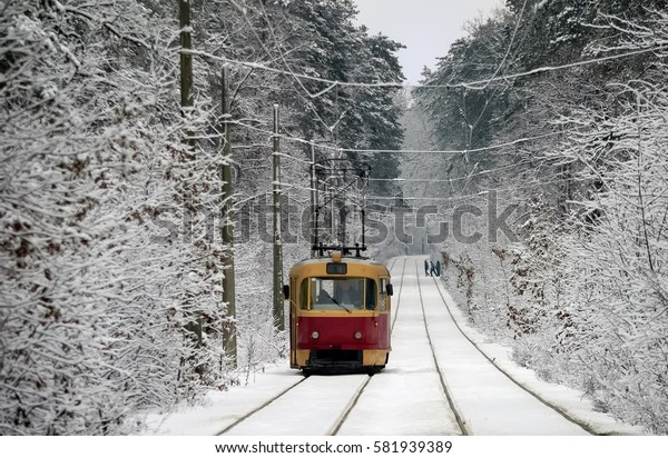 One red tram rides through the snow-covered road through the winter woods. In the distance, some people cross the road.