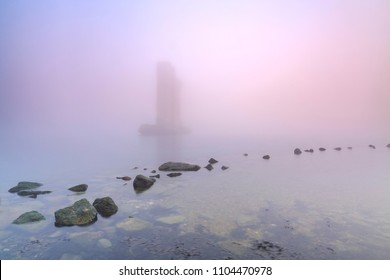 One of the remaining pillars of the storm surge barrier standing in water during a heavy dense foggy winter sunset at the delta works storm surge sea barrier Neeltje Jans in Zeeland, the Netherlands