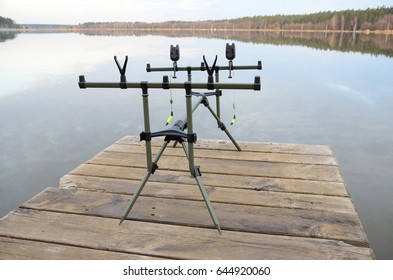 The one rod pod with two electronic bite alarms on a wooden pier by lake