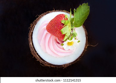 One round half coconut with strawberries and cream cheese on a black background. Health food concept