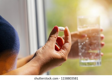 one round white pill in young female hand. Woman takes medicines with glass of water. Daily norm of vitamins, effective drugs, pharmacy and mental health concept image