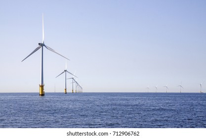 One row of 12 wind turbines in an offshore wind farm in the North Sea just off the coast of the Netherlands, on a clear day.