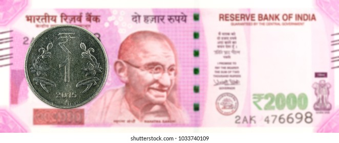 one rupee coin (2015) against 2000 indian rupee bank note obverse